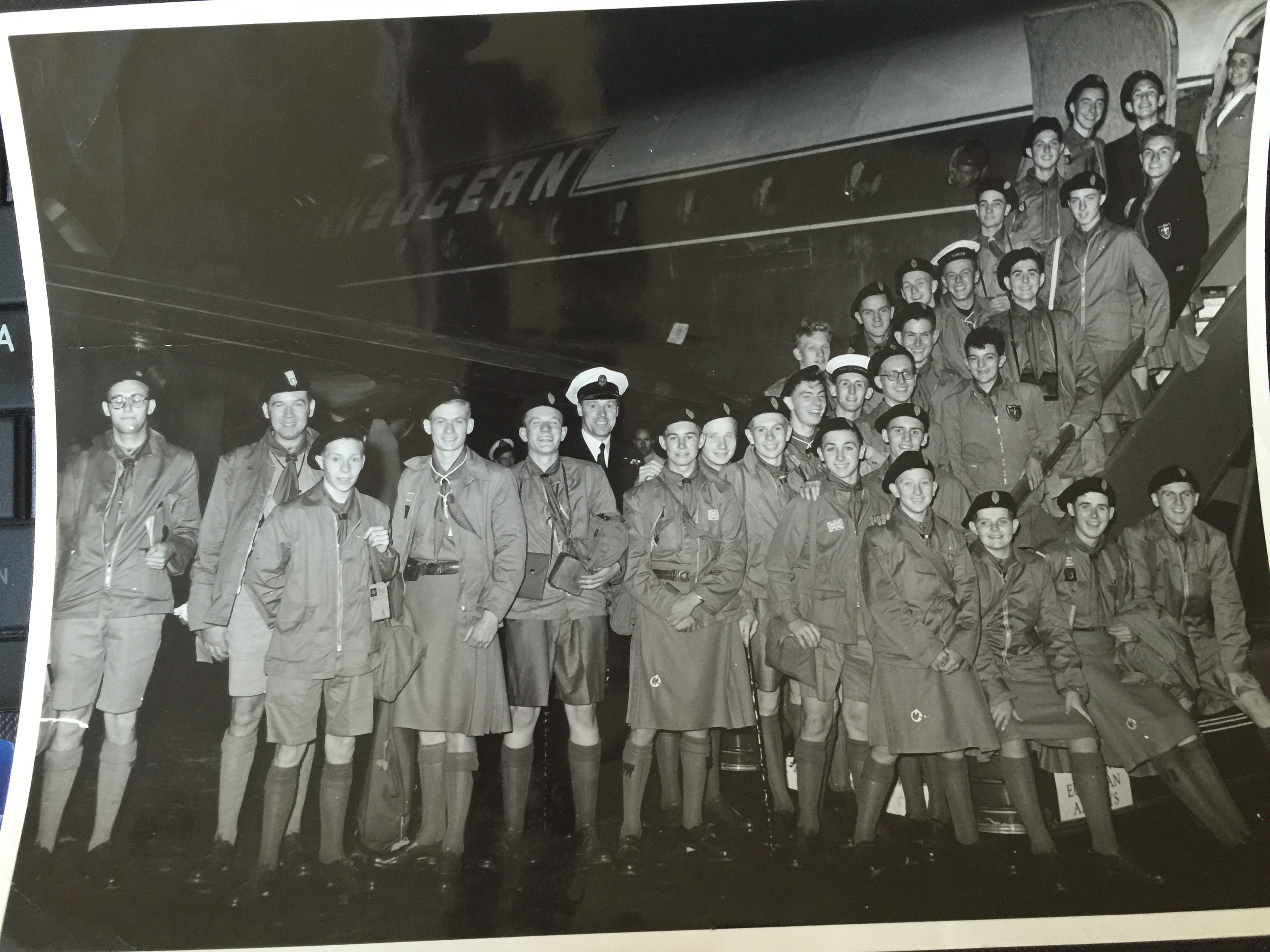 Thirty Scouts stand outside a passenger aircraft.