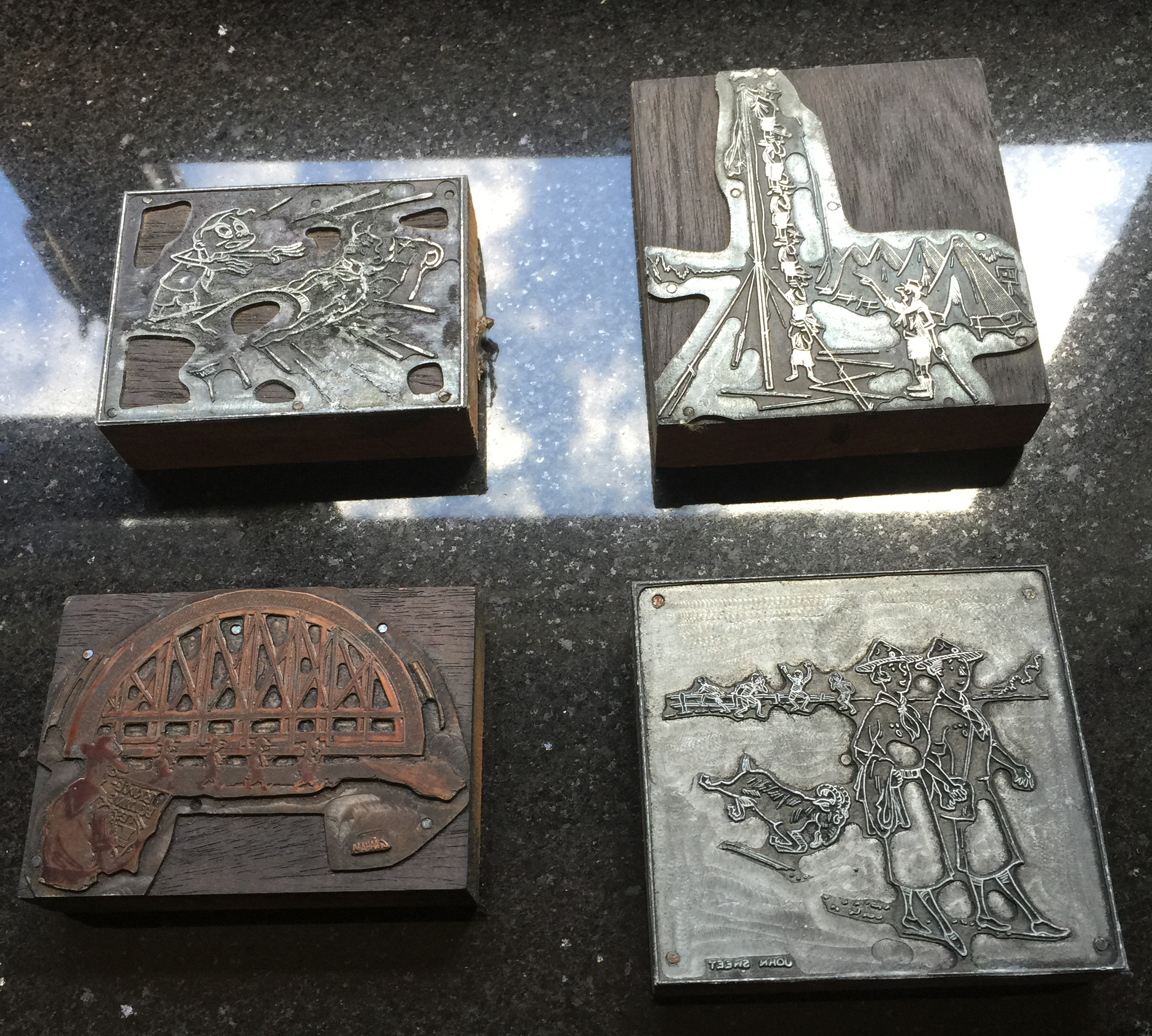 4 engraved metal pieces mounted on wood depicting in inverse different Scouting scenes.